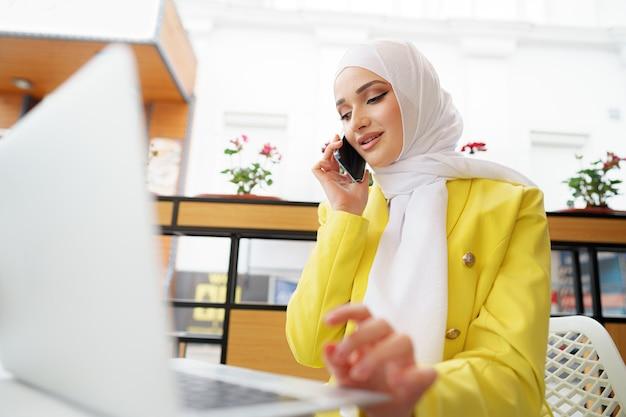 Jeune femme d'affaires musulmane en foulard assis dans un café et parlant au téléphone