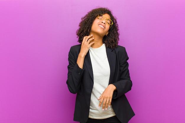 Jeune femme d'affaires noire se sentant stressée, frustrée et fatiguée, se frottant le cou douloureux, avec un regard inquiet et troublé