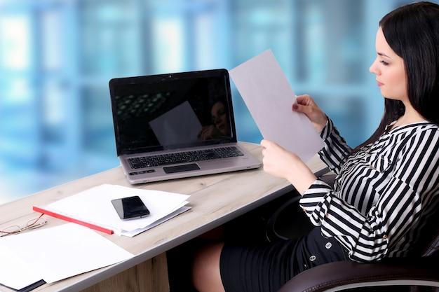 Jeune femme d'affaires avec ordinateur portable au bureau