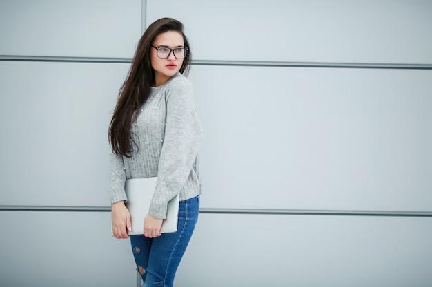 Une jeune femme d'affaires avec un ordinateur portable dans ses mains se tient dans la rue près d'un mur gris