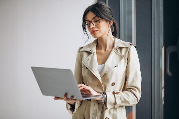 Jeune femme d'affaires avec ordinateur portable debout près de la fenêtre au bureau