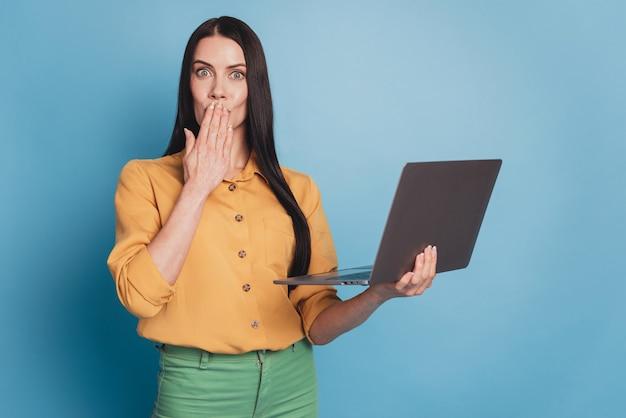 Jeune femme d'affaires avec ordinateur portable moderne en tenues de soirée sur fond bleu