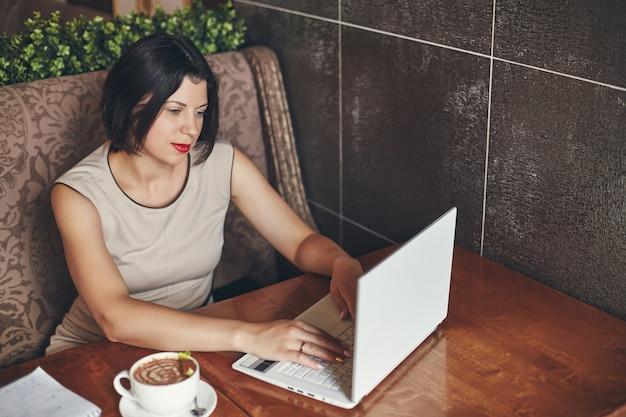 Jeune femme d'affaires avec ordinateur portable et ordinateur portable