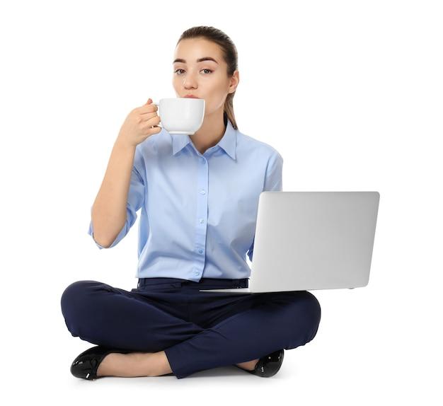 Jeune femme d'affaires avec ordinateur portable et tasse de café assis en position du lotus sur fond blanc