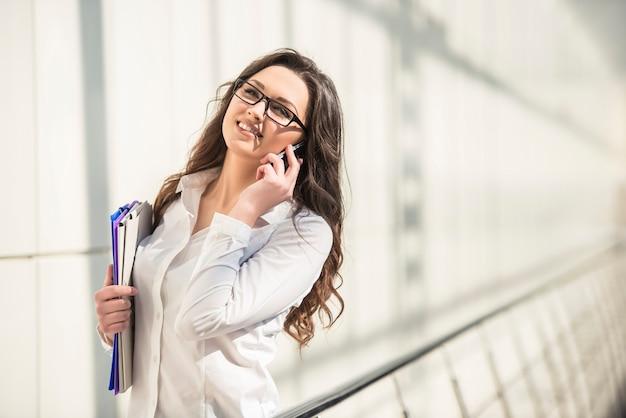 Jeune femme d'affaires parlant au téléphone et conserve le dossier.