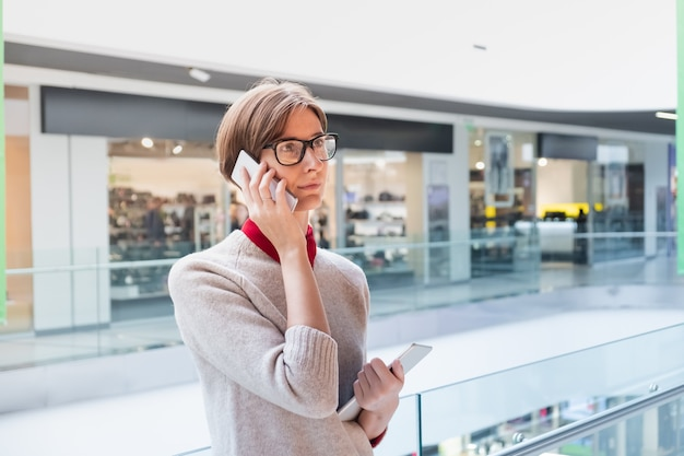 Jeune femme d'affaires parlant au téléphone dans un centre commercial. personne de sexe féminin dans des vêtements décontractés intelligents dans un grand magasin tenant une tablette