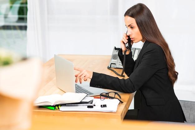 Jeune femme d'affaires, parler au téléphone en regardant un ordinateur portable au bureau