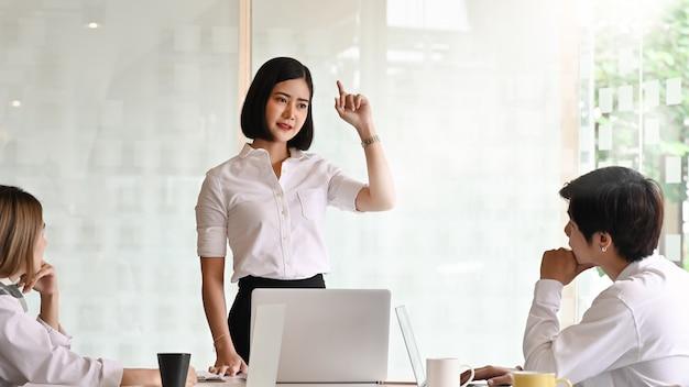 Jeune femme d'affaires passionnée expliquant son idée dans la salle de réunion