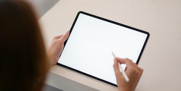 Jeune femme d'affaires passionnée travaillant sur son projet tout en utilisant une maquette de tablette