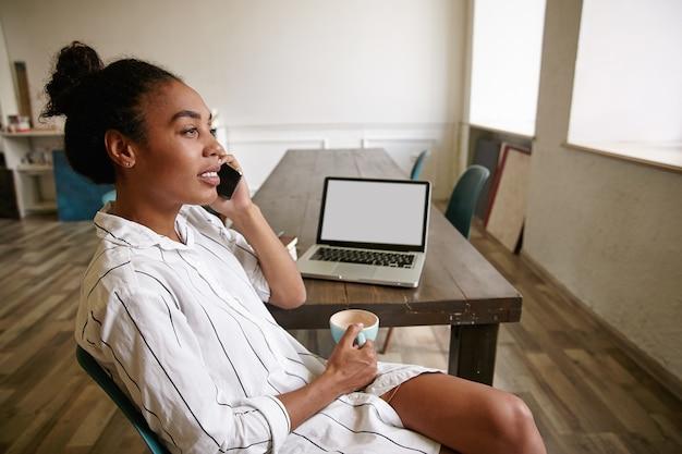 Jeune femme d'affaires à la peau sombre faisant une pause tout en travaillant dans la salle de réunion, tenant une tasse de café et appelant avec son smartphone, à la recherche de calme et concentré