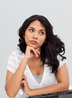 Jeune femme d'affaires pensant au bureau