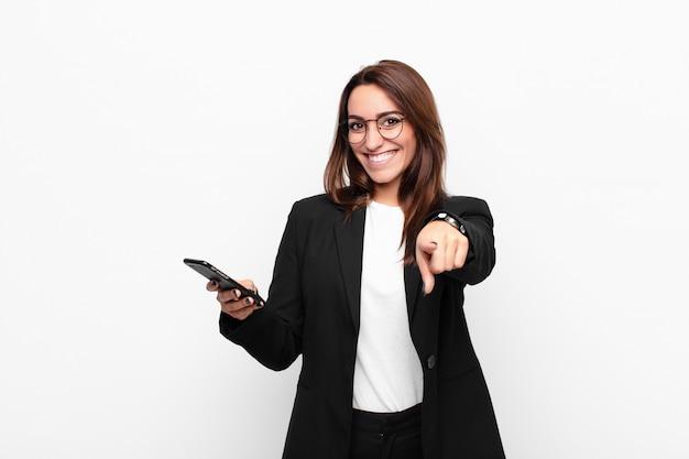 Jeune femme d'affaires pointant la caméra avec un sourire satisfait, confiant et amical, vous choisissant et tenant un téléphone mobile