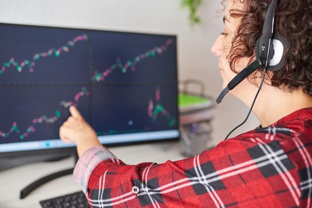 Une jeune femme d'affaires pointe vers un écran d'ordinateur avec des graphiques boursiers tout en portant un casque