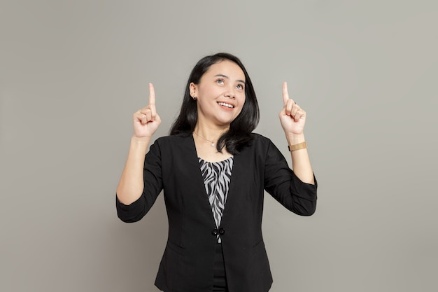 Jeune femme d'affaires portant un costume noir en levant et pointant vers le haut à deux mains