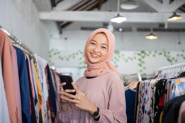 Une jeune femme d'affaires portant un hijab tenant un téléphone portable