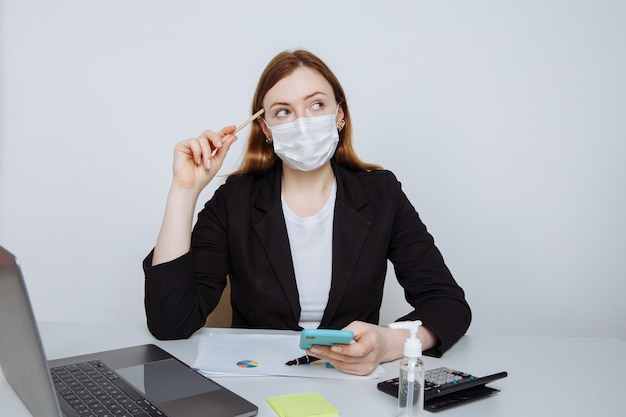 Jeune femme d'affaires portant un masque facial pensant une idée assise au bureau de travail dans la salle de bureau.