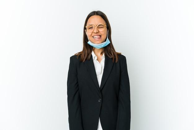 Jeune femme d'affaires portant un masque pour se protéger de covid isolé sur un mur blanc drôle et sympathique qui sort la langue