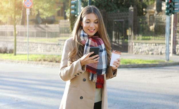 Jeune, femme affaires, porter, manteau, et, écharpe, marche, dans, rue ville
