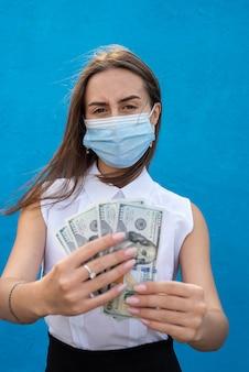 Jeune femme d'affaires porter un masque espiratoire tenant des billets d'un dollar isolés