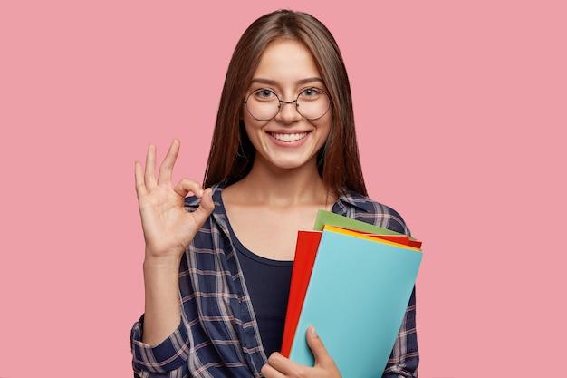Jeune femme d'affaires posant contre le mur rose avec des lunettes