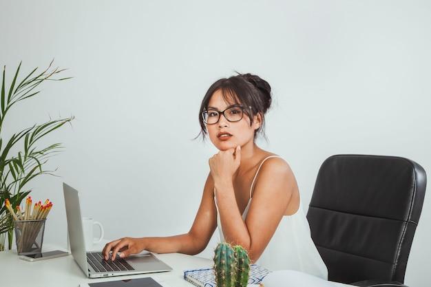 Jeune femme d'affaires posant à son bureau