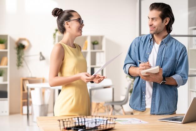 Jeune femme d'affaires positive en robe jaune debout par bureau avec ordinateur portable et analyse du rapport de vente avec un collègue
