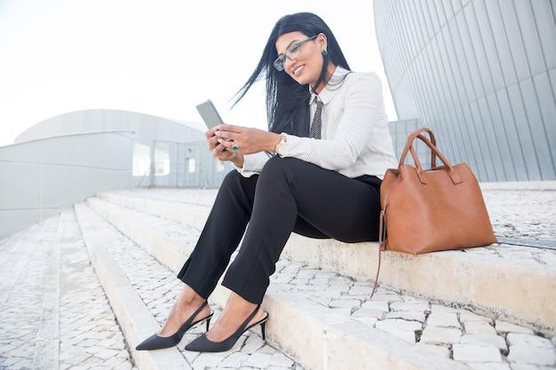 Jeune femme d'affaires positive utilisant un gadget pour travailler
