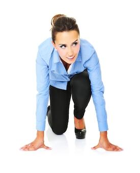 Une jeune femme d'affaires prête à démarrer une course sur fond blanc