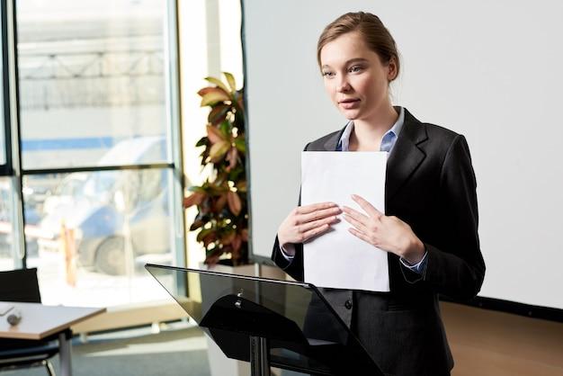 Jeune femme d'affaires prononçant un discours au forum