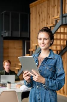 Jeune femme d'affaires prospère aux cheveux noirs debout devant la caméra dans l'environnement de travail et à l'aide du pavé tactile au bureau