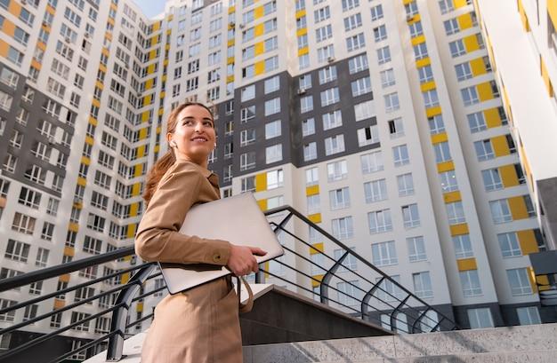 Jeune femme d'affaires prospère avec un ordinateur portable sur ses mains regarde par-dessus son épaule et sourit tout en grimpant les escaliers d'un immeuble de grande hauteur