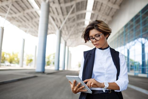 Jeune femme d'affaires prospère, regardant la tablette, debout près du centre d'affaires.