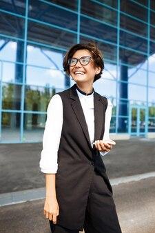 Jeune femme d'affaires prospère souriant, debout près du centre d'affaires.