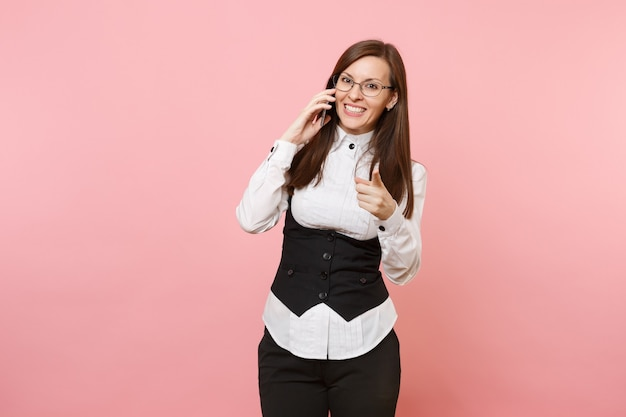 Jeune femme d'affaires prospère souriante dans des verres parlant sur téléphone portable pointant l'index isolé sur fond rose pastel. dame patronne. réalisation carrière richesse. copiez l'espace pour la publicité.