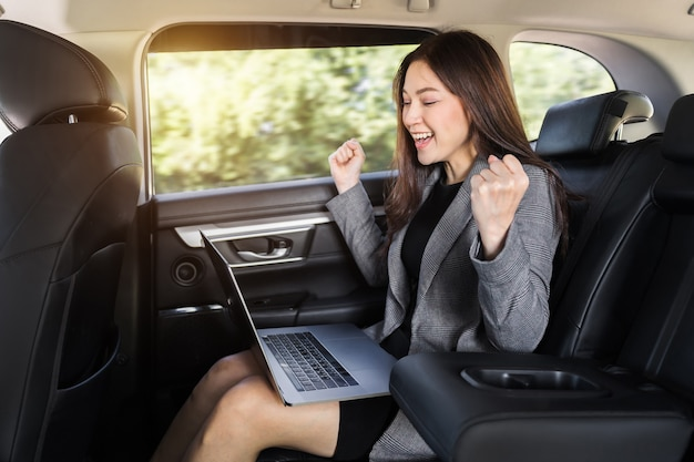 Jeune femme d'affaires prospère utilisant un ordinateur portable alors qu'elle était assise sur le siège arrière de la voiture