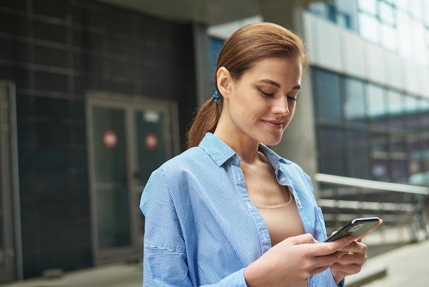 Une jeune femme d'affaires prospère vérifie ses e-mails sur son smartphone pendant une pause déjeuner à l'extérieur du bureau. femme d'affaires de la ville travaillant.