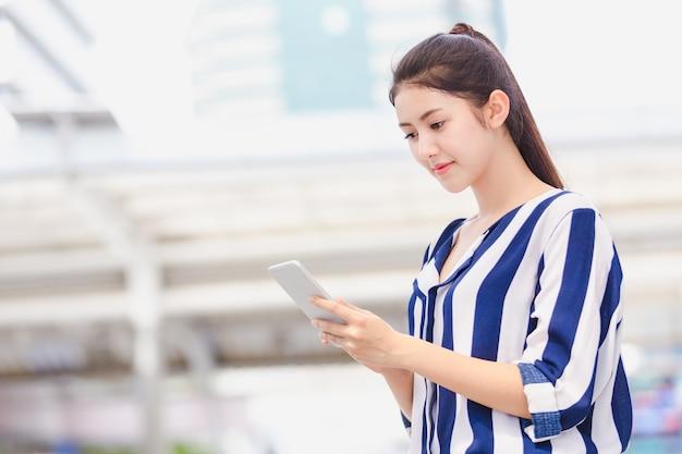 Jeune femme d'affaires à la recherche sur smartphone