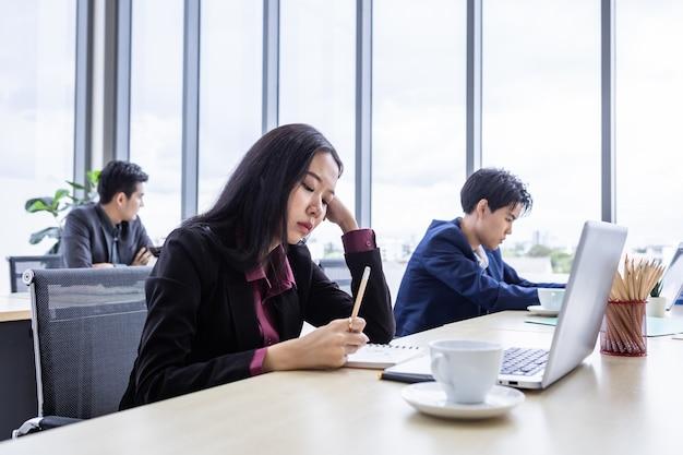 Jeune femme d'affaires réfléchie bouleversée stress sur le lieu de travail travaillant avec un ordinateur portable