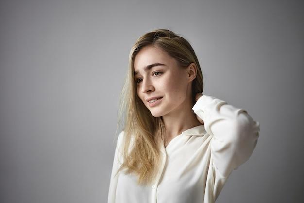 Jeune femme d'affaires réussie confiante vêtue d'un chemisier blanc en soie touchant l'arrière de son cou et une expression faciale pensive aile souriante, pensant à quelque chose au mur de studio blanc gris