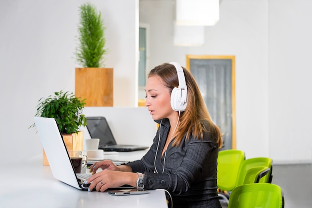 Jeune femme d'affaires réussie dans les écouteurs avec ordinateur portable surfer sur internet au bureau lumineux moderne