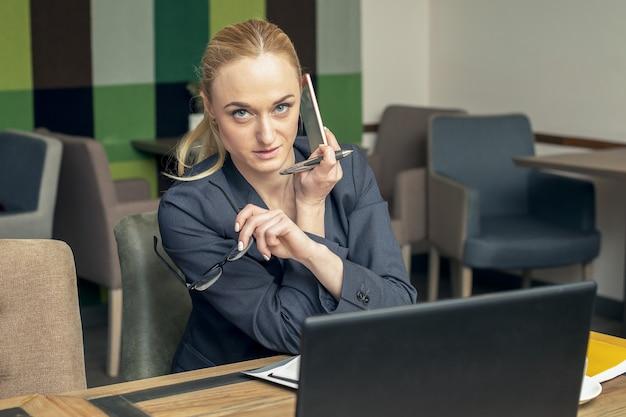 Jeune femme d'affaires réussie avec des lunettes parler sur le smartphone à la salle de réunion.