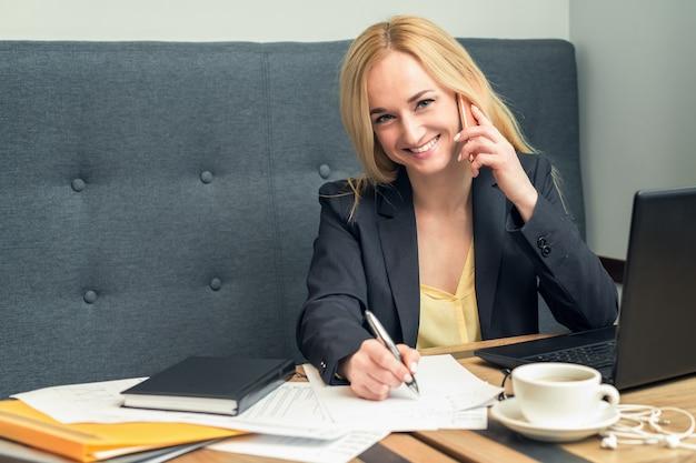 Jeune femme d'affaires réussie parle sur le smartphone au bureau.