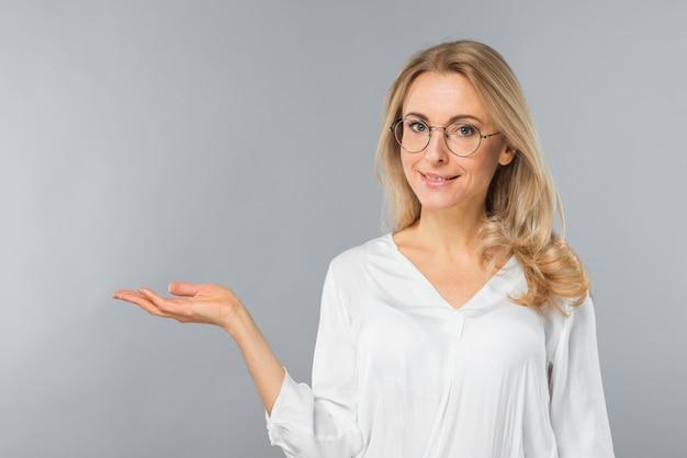 Jeune femme d'affaires réussie portant des lunettes présentant sur fond gris