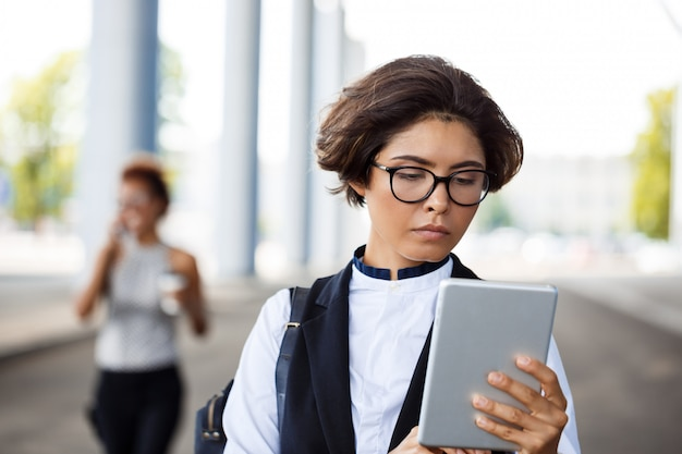 Jeune femme d'affaires réussie regardant tablette sur centre d'affaires.