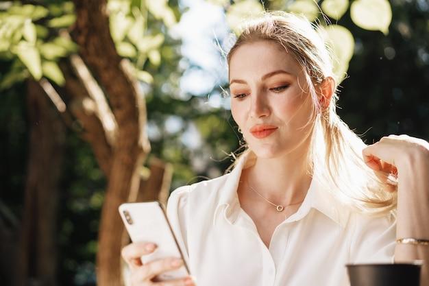 Jeune femme d'affaires réussie s'asseyant dans le café extérieur et utilisant le smartphone