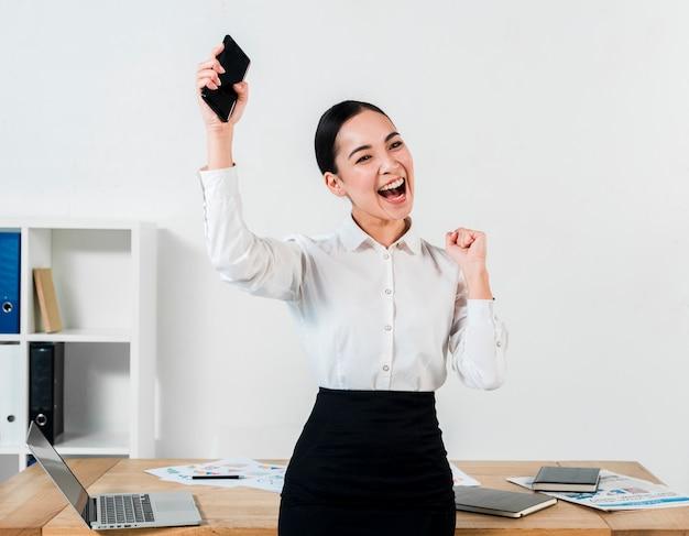 Jeune femme d'affaires réussie tenant mobile dans la main, serrant son poing au lieu de travail