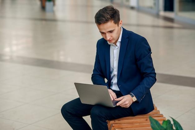 Jeune femme d'affaires réussie travaillant sur un ordinateur portable assis sur un banc