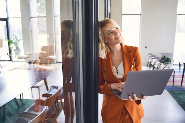 Jeune femme d'affaires rêveuse dans une veste élégante appuyée contre un mur du bureau
