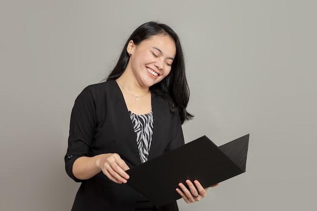 Jeune femme d'affaires riant tout en tenant le dossier