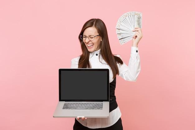 Jeune femme d'affaires riante tenant un paquet de dollars, de l'argent en espèces et un ordinateur portable avec un écran vide vierge isolé sur fond rose. dame patronne. réalisation carrière richesse. espace de copie.